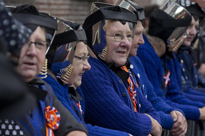 Dutch women in traditional clothes line the route that King Willem-Alexander traveled during a ceremony for the officially opening of the new parliamentary year in The Hague, Netherlands, Tuesday, Sept. 17, 2013. The King outlined the government's plan and budget policies for the year ahead. (AP Photo/Peter Dejong)