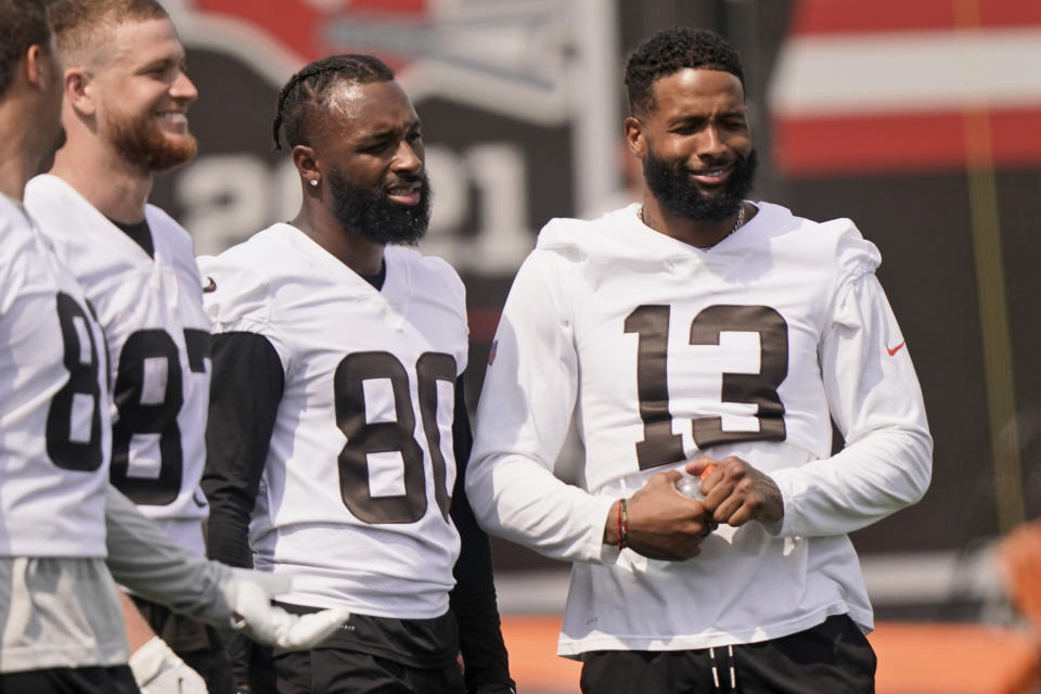 Cleveland Browns wide receiver Jarvis Landry (80) and Cleveland Browns wide receiver Odell Beckham Jr. (13) watch during an NFL football practice, Saturday, July 31, 2021, in Berea, Ohio. (AP Photo/Tony Dejak)