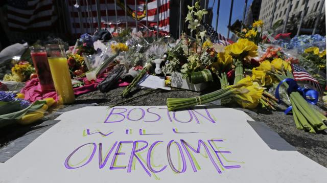 Flowers and signs adorn a barrier at Boylston Street near the of finish line of the 2013 Boston Marathon bombing. (AP Photo/Charles Krupa)