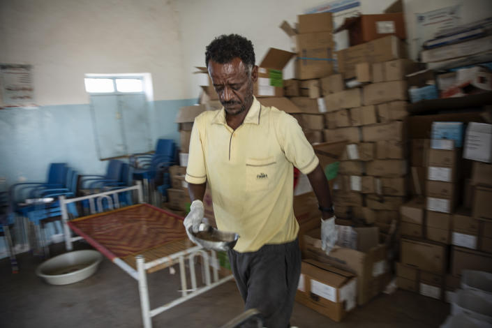 Surgeon and doctor-turned-refugee, Dr. Tewodros Tefera, sanitizes medical equipment, at the Sudanese Red Crescent clinic in Hamdayet, eastern Sudan, near the border with Ethiopia, on March 22, 2021. (AP Photo/Nariman El-Mofty)