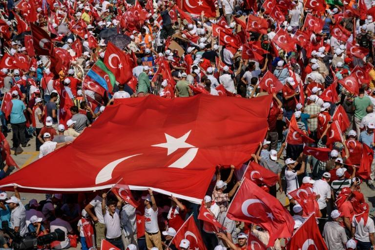 Demonstrators unfurl a giant Turkish flags during a pro-democracy rally in Istanbul, on August 7, 2016