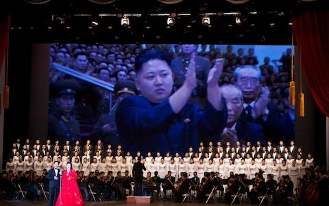 Kim Jong Un is projected on a screen behind an orchestra and choir during a performance in Pyongyang, North Korea - Credit: AP Photo/David Guttenfelder