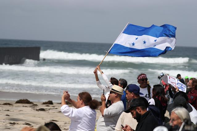 <p>Supporters wave a Honduran flag on the U.S. side of the U.S.-Mexico border wall at Border Field State Park as members of a migrant caravan from Central America stand on the other side, in San Diego, California, April 29, 2018. (Photo: Lucy Nicholson/Reuters) </p>