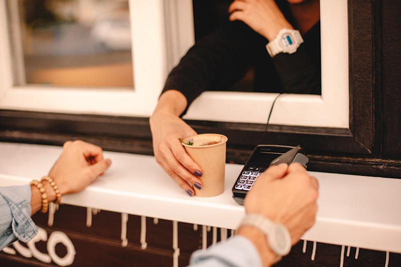 Customer making payment with credit card buying coffee on city street