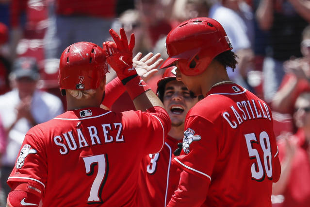 Cincinnati Reds' Eugenio Suarez (7) celebrates with Scooter Gennett, center, and Luis Castillo (58) after hitting a grand slam off Pittsburgh Pirates starting pitcher Ivan Nova in the third inning of a baseball game, Thursday, May 24, 2018, in Cincinnati. (AP Photo/John Minchillo)