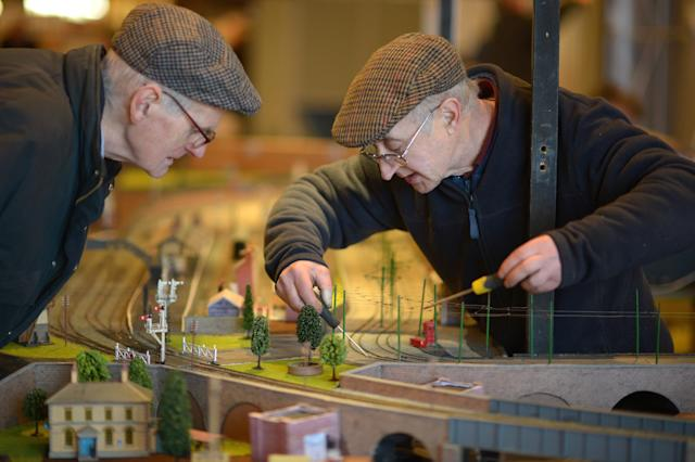 GLASGOW, SCOTLAND - FEBRUARY 21: Bernard Manson and John McMullan tinker with a display as model enthusiasts gather for the Model Rail Scotland exhibition on February 21, 2013 in Glasgow, Scotland. Model railway clubs from all corners of the UK and parts of Europe will be displaying over 50 model railway layouts at this year's event held at The Scottish Exhibition Centre in Glasgow from February 22nd to the 24th. (Photo by Jeff J Mitchell/Getty Images)