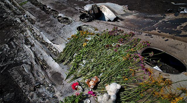 Toys and flowers are placed on the charred fuselage at the crash site of Malaysia Airlines Flight 17. Photo: AP.