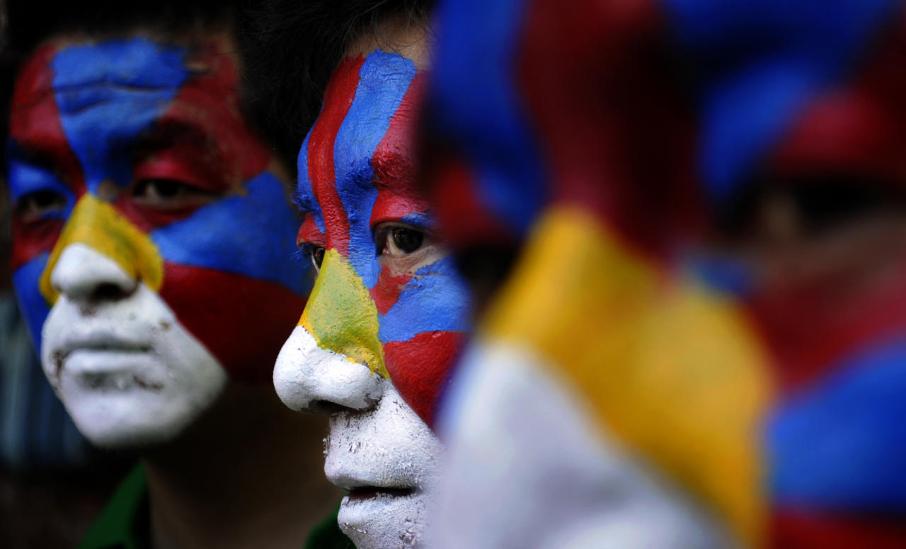 Tibetan exiles, with faces painted in the Tibetan flag colors, participate in a rally to express solidarity with the plight of the people in Tibet, in New Delhi, India, Wednesday, Oct. 19, 2011. Tibetan spiritual leader The Dalai Lama on Wednesday fasted and led prayers in honor of nine Tibetans who set themselves on fire in apparent protest against China's tight grip over Buddhist practices in Tibet. (AP Photo/Tsering Topgyal)