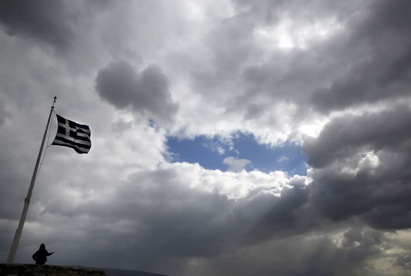A tourist stands under a Greek flag atop the Acropolis hill in Athens February 18, 2015. REUTERS/Yannis Behrakis