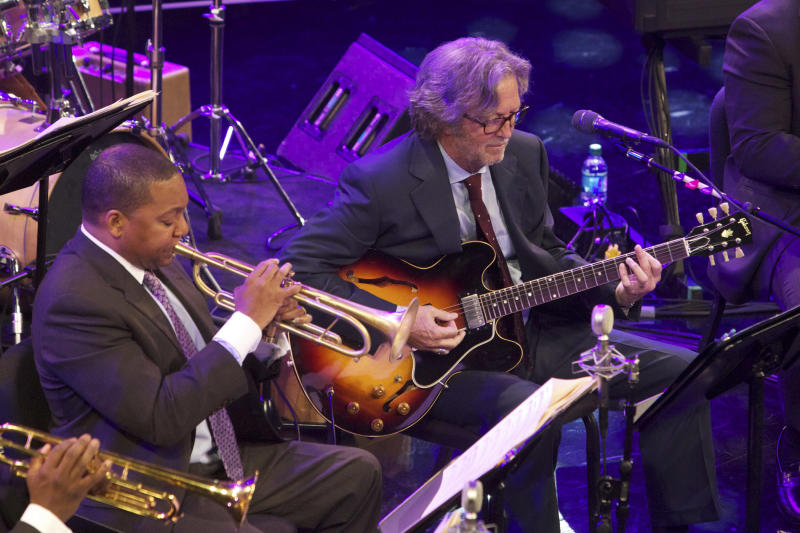 FILE - This Thursday, April 7, 2011 file photo courtesy of Julie Skarratt shows Jazz at Lincoln Center Artistic Director Wynton Marsalis, left, and musician Eric Clapton during Jazz at Lincoln Center's 2011 Annual Gala in New York. Although Marsalis comes from the worlds of jazz and classical music, and Clapton is a member of the Rock and Roll Hall of Fame, Marsalis says their recent collaboration wasn't that unusual because they both have something that unifies them — their love of the blues.    (AP Photo/Julie Skarratt, File)
