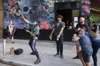 A man takes photos with friends outside a bar in the Hell's Kitchen neighborhood of New York, Friday, May 29, 2020, during the coronavirus pandemic. People are beginning to gather in small groups as the city begins to reopen. (AP Photo/Mark Lennihan)
