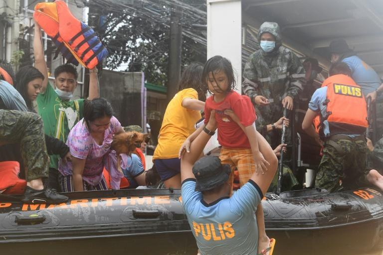 Rescuers evacuate residents from their flooded homes