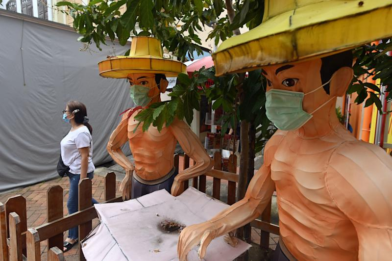 A woman walks past a display of two cultural figurines of men wearing masks in Singapore on 12 June, 2020. (PHOTO: AFP via Getty Images)