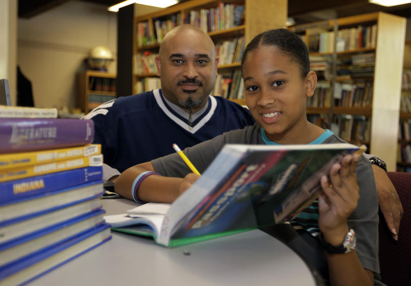 In this Aug. 7, 2012 photo, Phillip Covington, left, poses with his son Giovanni as he works on a mathematics lesson in the library of Todd Academy in Indianapolis. Struggling Indiana public school districts are buying billboard space, airing radio ads and even sending principals door-to-door in an unusual marketing campaign aimed at persuading parents not to move their children to private schools as the nation's largest voucher program doubles in size. (AP Photo/Michael Conroy)
