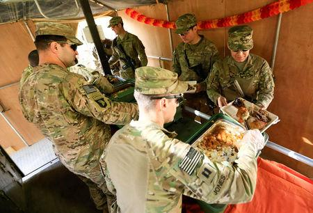 U.S. soldiers serve food to fellow soldiers as they celebrate Thanksgiving Day inside the U.S. army base in Qayyara, south of Mosul, Iraq November 24, 2016. REUTERS/Thaier Al-Sudani