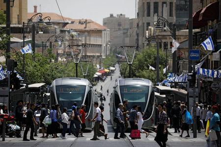 Pedestrians cross a street next to the light rail trams in Jerusalem May 11, 2017. Picture taken May 11, 2017. REUTERS/Amir Cohen