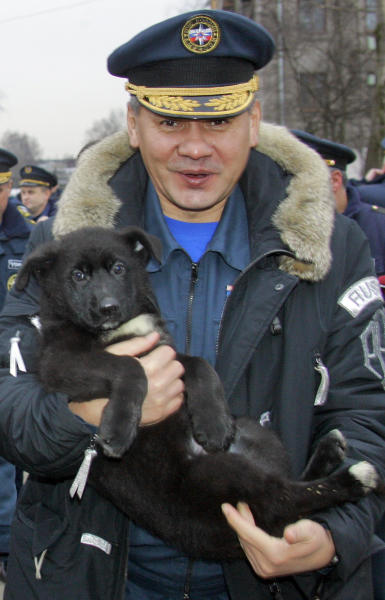 FILE - In this Tuesday, Dec. 26, 2006 file photo, the then Russia's Emergency Situations Minister Sergei Shoigu holds a German Shepherd puppy as he gives him to the Northwestern Regional Center of Russia's Emergency Situations Ministry moving to new headquarters in St. Petersburg, Russia. Russian President Vladimir Putin has fired the country's defense minister two weeks after a criminal probe was opened into alleged fraud in the sell-off of military assets. Putin made the announcement of Anatoly Serdyukov's dismissal on Tuesday Nov. 6, 2012 in a meeting with Moscow regional governor Sergei Shoigu, whom he appointed as the new minister. (AP Photo/Dmitry Lovetsky, file)