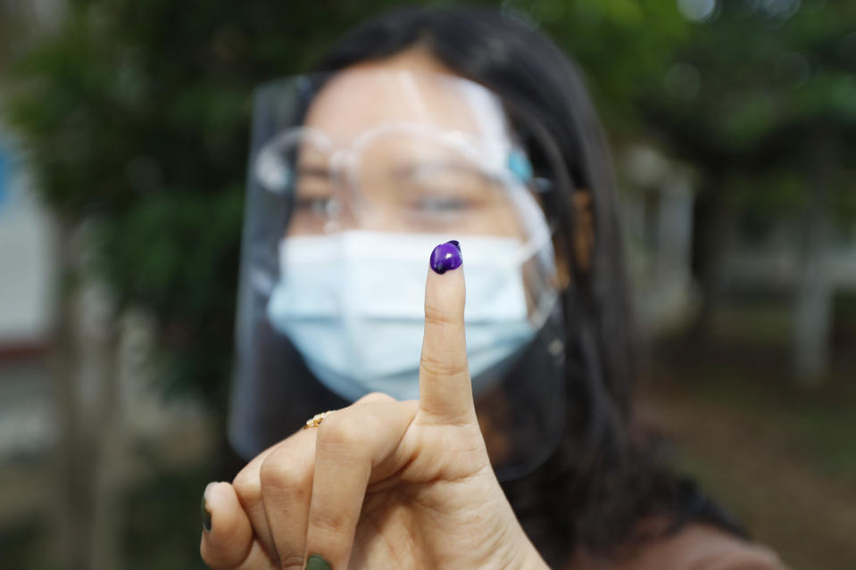FILE - In this Sunday, Nov. 8, 2020 file photo, a woman displays her finger marked with ink indicating she has voted as she leaves a polling station, in Naypyitaw, Myanmar. A major election monitoring organization says last November's election results in Myanmar were representative of the will of the people, rejecting the military's allegations of massive fraud that served as its justification for seizing power. ANFREL, the Asian Network for Free Elections, said in a 171-page report said procedural safeguards helped make the polling process transparent and reliable. (AP Photo/Aung Shine Oo, File)