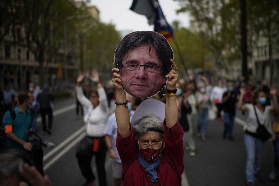 A woman holds a cardboard cut out of the head of former Catalan leader Carles Puigdemont during a protest in support of Puigdemont outside the Italian consulate in Barcelona, Spain, Friday, Sept. 24, 2021. Puigdemont, who fled Spain after a failed secession bid for the northeastern region in 2017, was detained Thursday in Sardinia, Italy, his lawyer said. Puigdemont, who lives in Belgium and now holds a seat in the European Parliament, has been fighting extradition to Spain, which accused him and other Catalan independence leaders of sedition. (AP Photo/Joan Mateu)