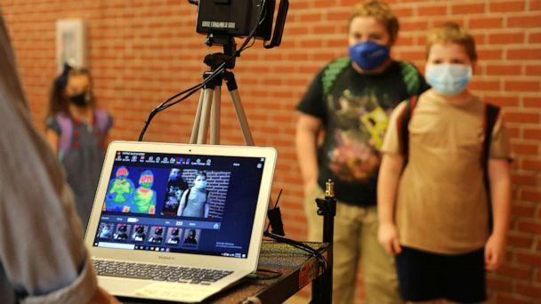 PHOTO: Corinth Elementary School students have their temperature checked by a thermal scanner as they arrive for their first day back to school Monday, July 27, 2020 in Corinth, Miss. (The Northeast Mississippi Daily Journal via AP)