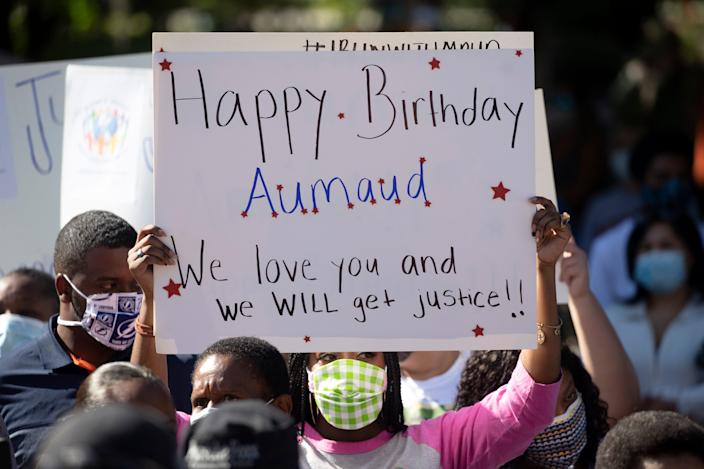 A woman holds a sign during a rally protesting the shooting of Ahmaud Arbery.