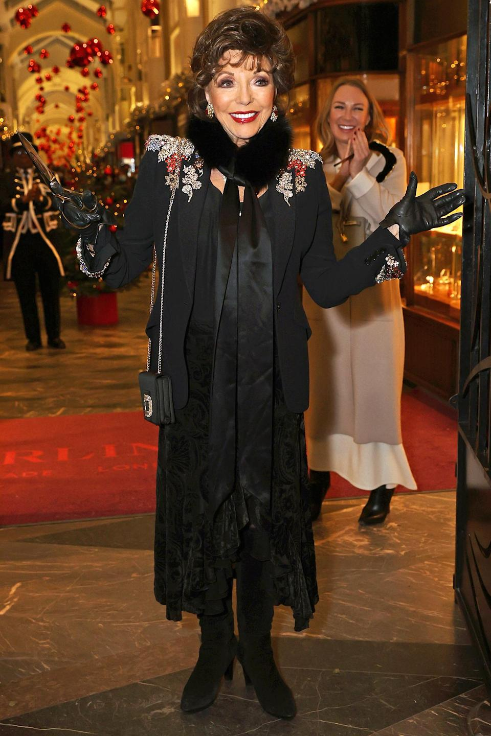 <p>Dame Joan Collins cuts the ribbon at the Burlington Arcade in London.</p>