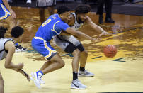 UCLA guard Jaylen Clark (0) tries to steal the ball from Oregon guard LJ Figueroa during the first half of an NCAA college basketball game Wednesday, March 3, 2021, in Eugene, Ore. (AP Photo/Andy Nelson)