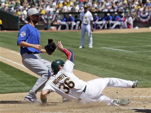 Oakland Athletics' Derek Norris, right, scores on a passed ball by Chicago Cubs catcher Welington Castillo next to Chicago Cubs reliever Matt Guerrier, left, during the seventh inning of an MLB baseball game on Thursday, July 4, 2013, in Oakland, Calif. (AP Photo/Marcio Jose Sanchez)