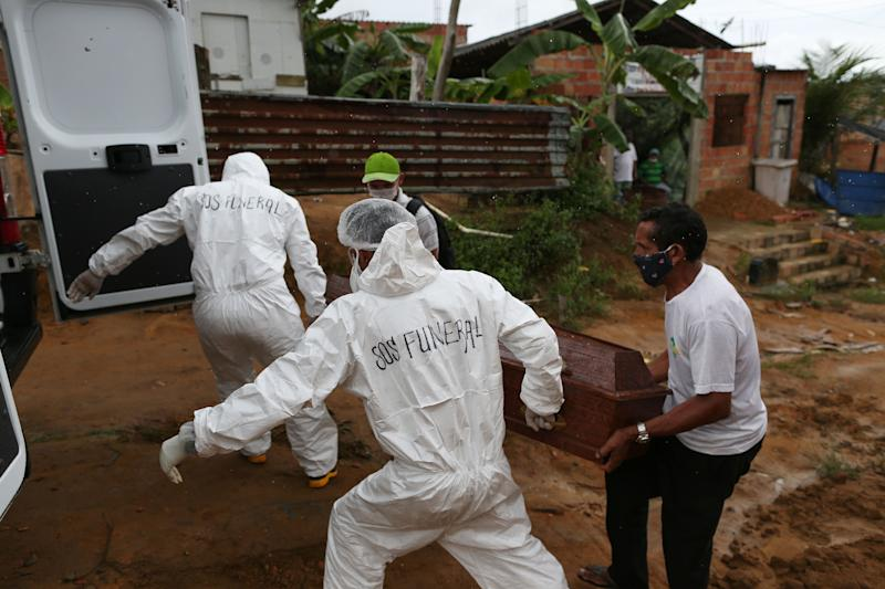 Municipal workers remove the body of 92-year-old Estevao Pereira from his home in Manaus, in the Brazilian state of Amazonas, on May 4, 2020 after he died during the night showing symptoms of the COVID-19 novel coronavirus. - The novel coronavirus has killed at least 249,372 people worldwide since the outbreak first emerged in China last December, according to a tally from official sources compiled by AFP at 1900 GMT on Monday. (Photo by Michael DANTAS / AFP) (Photo by MICHAEL DANTAS/AFP via Getty Images)