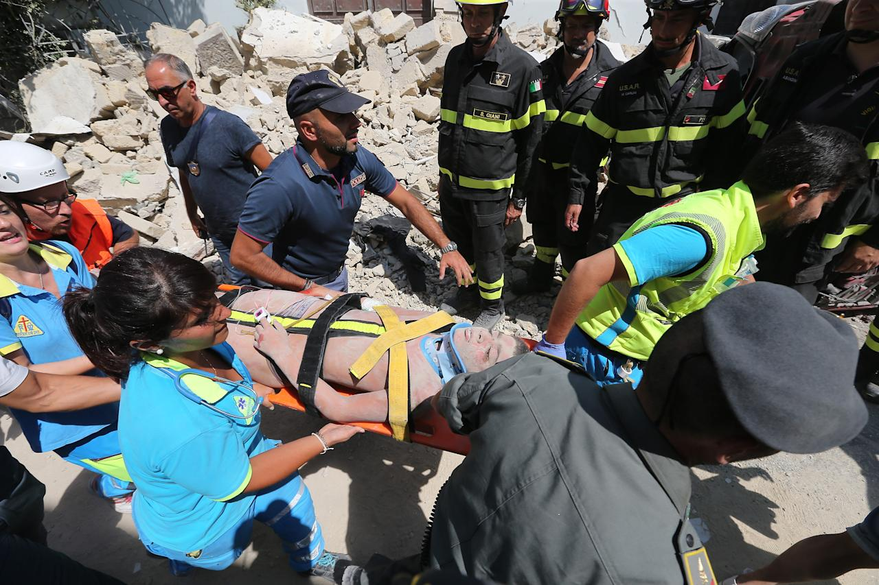 <p>Italian emergency workers evacuate on a stretcher a boy who was was trapped by rubble, in Casamicciola Terme, on the Italian island of Ischia, on August 22, 2017, after an earthquake hit the popular Italian tourist island off the coast of Naples, causing several buildings to collapse overnight. (Photo: Marco Cantile/NurPhoto via Getty Images) </p>