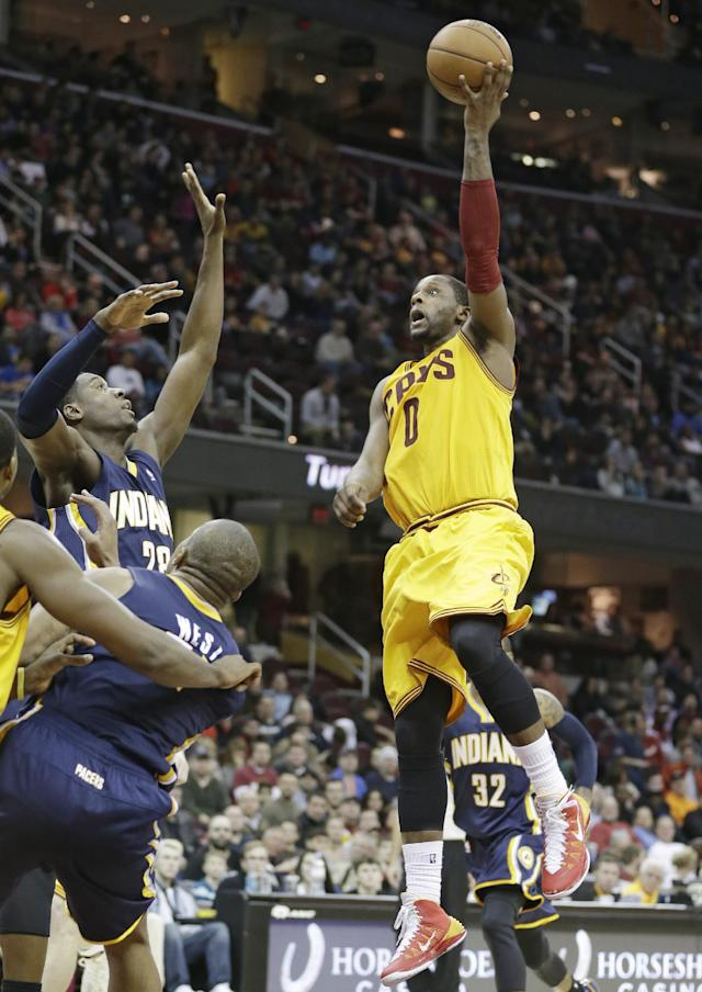 Cleveland Cavaliers' C.J. Miles (0) jumps to the basket against Indiana Pacers' Ian Mahinmi (28), of France, and David West during the third quarter of an NBA basketball game Sunday, Jan. 5, 2014, in Cleveland. The Pacers won 82-78. (AP Photo/Tony Dejak)