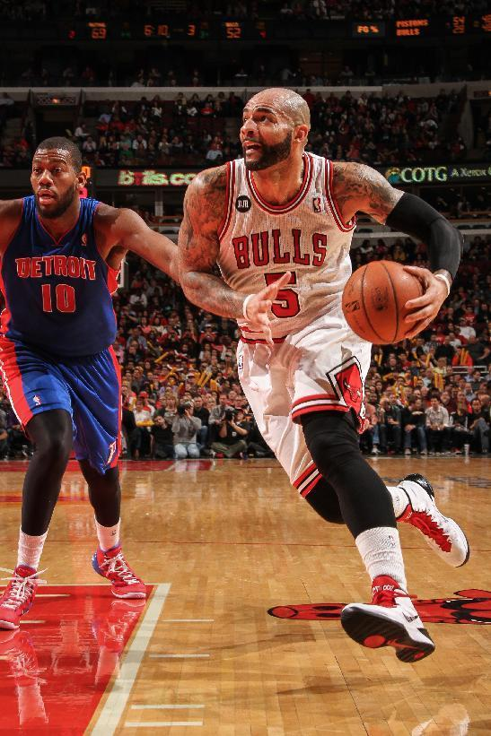 CHICAGO, IL - APRIL 11: Carlos Boozer #5 of the Chicago Bulls takes the ball past Greg Monroe #10 of the Detroit Pistons on April 11, 2014 at the United Center in Chicago, Illinois. (Photo by Ray Amati/NBAE via Getty Images)