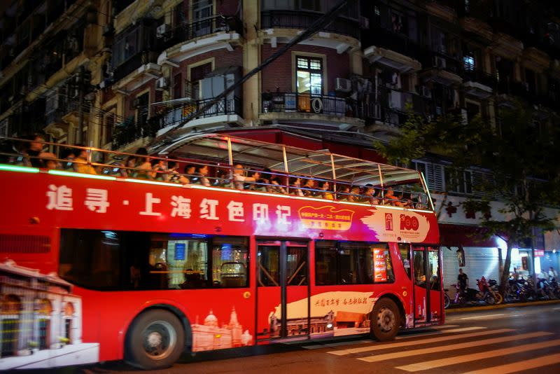 Tourists ride on a bus marking the 100th founding anniversary of the Communist Party of China, in Shanghai