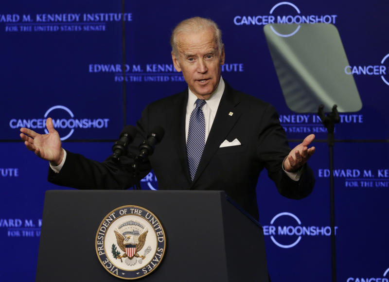 """FILE - In this Oct. 18, 2016 file photo, Vice President Joe Biden speaks at the Edward M. Kennedy Institute for the United States Senate in Boston, about the White House's cancer """"moonshot"""" initiative — a push to throw everything at finding a cure within five years. Biden's defining venture since leaving the Obama White House is the Biden Cancer Initiative, a nonprofit aimed at speeding a cancer cure in memory of his son. (AP Photo/Elise Amendola)"""