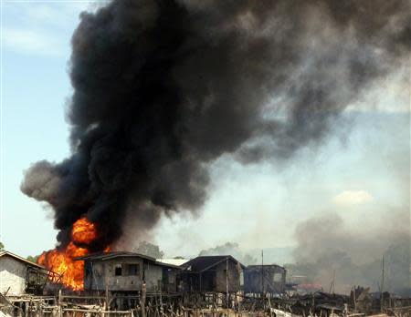 Smoke billows as stilt houses burn in fires caused by fighting between government soldiers and Muslim rebels of the MNLF in the outskirts of Zamboanga city