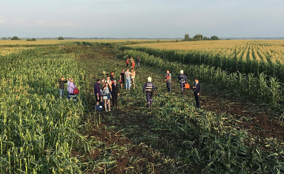 Rescuers, passengers and crew stand in the field after being evacuated from the jet. (Reuters)