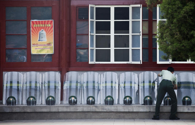 A Chinese paramilitary policeman wipes off helmets and shields placed outside the police barracks near Tiananmen Gate on the anniversary of the deadly 1989 crackdown on pro-democracy protests centered on Tiananmen Square, in Beijing, China Monday, June 4, 2012.(AP Photo/Andy Wong)
