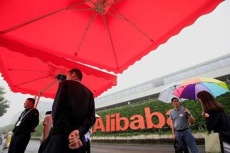 FILE PHOTO: People stand near a sign of Alibaba Group at its campus in Hangzhou