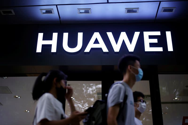 People walk past a Huawei store at a shopping mall in Shanghai