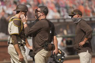 San Diego Padres catcher Jason Castro, left, is checked by a trainer as manager Jayce Tingler, right, looks on in the sixth inning of a baseball game against the San Francisco Giants, Sunday, Sept. 27, 2020, in San Francisco. Castro left the game and was replaced by Austin Nola. (AP Photo/Eric Risberg)