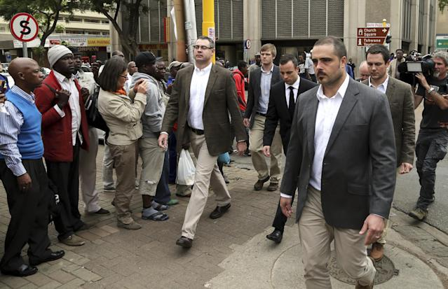 Oscar Pistorius, middle, accompanied by relatives walks towards the high court in Pretoria, South Africa, Wednesday, April 9, 2014. Pistorius is charged with murder for the shooting death of his girlfriend, Reeva Steenkamp on Valentine's Day in 2013. (AP Photo/Themba Hadebe)