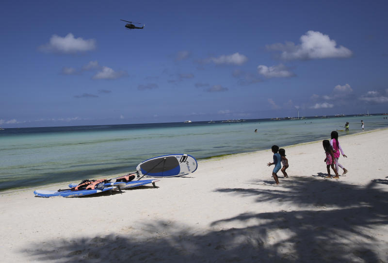 """Children watch as a military helicopter passes by the country's most famous beach resort island of Boracay, in central Aklan province, Philippines Wednesday, April 25, 2018, a day before the government implements its temporary closure. Thousands of workers will be affected when Boracay will be closed after Philippine President Rodrigo Duterte orders its closure on April 26 for up to six months after saying the waters off its famed white-sand beaches had become a """"cesspool"""" due to overcrowding and development. (AP Photo/Aaron Favila)"""