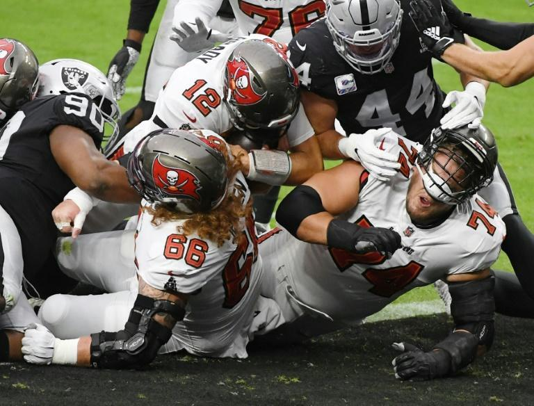 Quarterback Tom Brady, 12, of the Tampa Bay Buccaneers follows centre Ryan Jensen, left, and offensive guard Ali Marpet, right, into the end zone to score a touchdown against the Las Vegas Raiders in the first half of their game at Allegiant Stadium