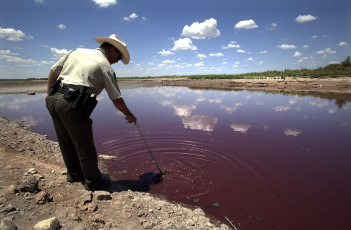 Texas State Park police officer Thomas Bigham reaches down into what remains of O.C. Fisher Lake Wednesday, Aug. 3, 2011, in San Angelo, Texas. A bacteria called Chromatiaceae has turned the 1-to-2 acres of lake water remaining the color red. A combination of the long periods of 100 plus degree days and the lack of rain in the drought -stricken region has dried up the lake that once spanned over 5400 acres. (AP Photo/Tony Gutierrez)