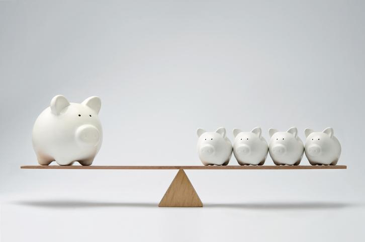 A balanced scale with a giant piggy bank on one end and four smaller piggy banks on the other.