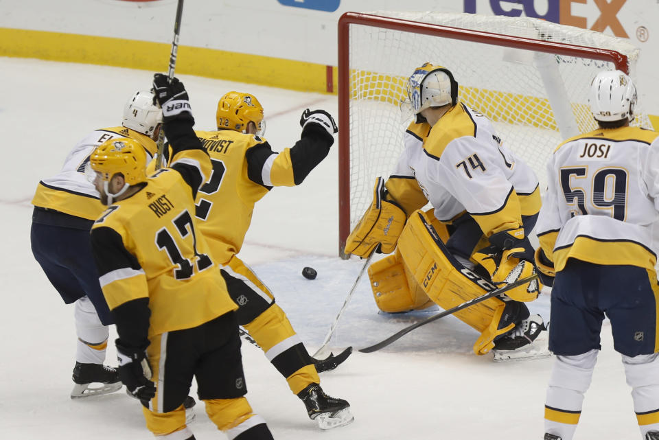 Pittsburgh Penguins' Bryan Rust (17) and Patric Hornqvist (72) celebrate a goal by Kris Letang on Nashville Predators goaltender Juuse Saros (74) during the first period of an NHL hockey game Saturday, Dec. 28, 2019, in Pittsburgh. (AP Photo/Keith Srakocic)