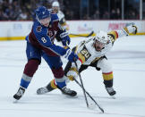 Colorado Avalanche defenseman Cale Makar (8) and Vegas Golden Knights center Chandler Stephenson (20) reach for the puck during the third period in Game 2 of an NHL hockey Stanley Cup second-round playoff series Wednesday, June 2, 2021, in Denver. (AP Photo/Jack Dempsey)