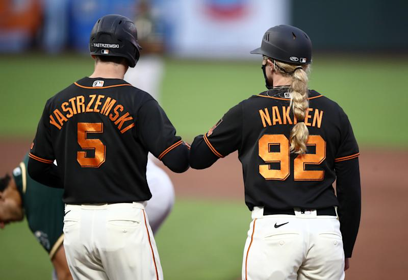 SAN FRANCISCO, CALIFORNIA - JULY 21: First base coach Alyssa Nakken elbow bumps Mike Yastrzemski #5 of the San Francisco Giants after he walked in the third against the Oakland Athletics during their exhibition game at Oracle Park on July 21, 2020 in San Francisco, California. (Photo by Ezra Shaw/Getty Images)