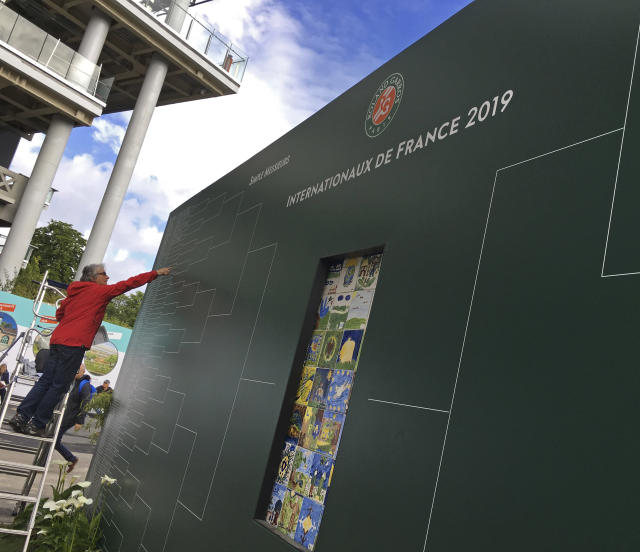 "In this Tuesday, May 28, 2019, photo, a man puts the names of players who went through the next round on a board which bears the original name of the tournament, Internationaux de France, at the the French Open tennis tournament at the Roland Garros stadium in Paris. English-speakers tend to go with ""French Open,"" even though that's not used by the event itself. Most of the rest of the world says ""Roland Garros,"" which is the facility that hosts the tournament and is named in memory of a World War I fighter pilot. But what hardly ever is uttered is the original name of the tournament ""Internationaux de France"", which translates to ""International Championships of France."" (AP Photo/Peter Dejong)"