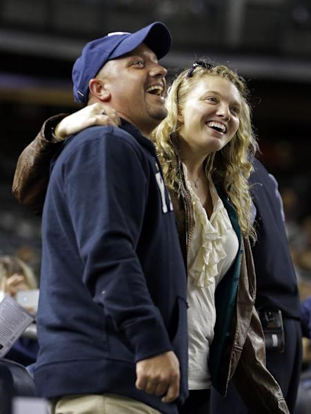 "Two fans embrace while singing ""Sweet Caroline"" as a tribute to the victims of the Boston Marathon explosions after the third inning of a baseball game between the New York Yankees and the Arizona Diamondbacks at Yankee Stadium in New York, Tuesday, April 16, 2013. The song by Neil Diamond has been a longtime fixture as a fan sing-along during the bottom of the eighth inning of Boston Red Sox games. In big ways and small, New York is putting aside its heated and historical rivalry with Boston in a show of support after the Boston Marathon explosions. (AP Photo/Kathy Willens)"